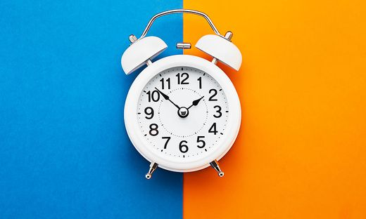 White vintage alarm clock on blue-orange background. Top view, copy space. Daylight saving concept.