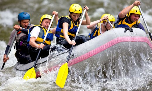 Group of people paddling while whitewater rafting