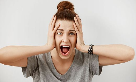 Young woman screaming in terror with hands on her head, mouth wide open looking in panic at the camera. Close up portrait of irritated female shouting, covering her ears, angry with noisy neighbours