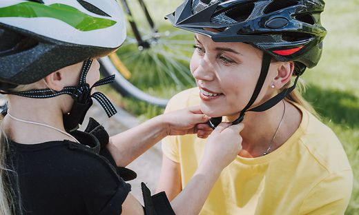 Little girl helping mother to put on bicycle helmet
