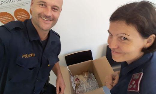 Die Polizisten Joachim List und Birgit Neubauer mit der verletzten Katze, die sie in eine Schachtel gelegt haben