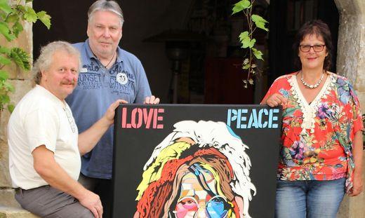 Andres Klimbacher, Roman Kobald und Burgfrau Astrid Pranger mit einem Bild, das Janis Joplin zeigt. Die Drei holen das richtige Woodstock in die Herzogburg