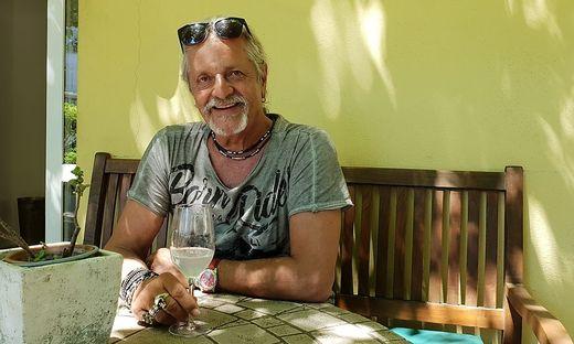 Thomas Spitzer auf einer Bank im Gastgarten sitzend mit einem Glas Mineral-Zitron in der Hand