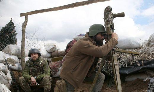 Ein ukrainischer Soldat blickt an der ostukrainischen Front mit den von Russland unterstützten Separatisten durch ein Periskop