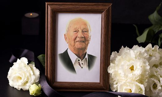 Wooden mourning photo frame next to white flowers on black background