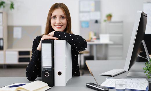 Eine Frau sitzt in einem Büro am Schreibtisch, ihre Arme stützt sie auf zwei Aktenmappen