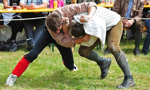 Zwei Ringer versuchen sich in einem Kampf gegenseitig zu Boden zu ringen