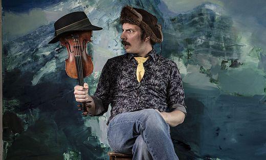 Manfred Plessl mit seiner Geige und einem Bild von Musikerkollege Richard Klammer im Hintergrund
