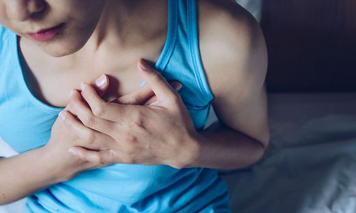 Close-up of woman having suffering from chest pain or heart attack.