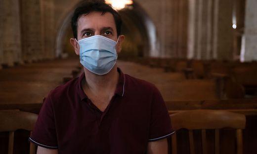 Mann trägt Maske in Kirche