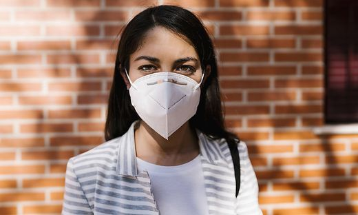 Confident woman wearing protective face mask against brick wall during COVID-19 model released Symbolfoto EGAF01011