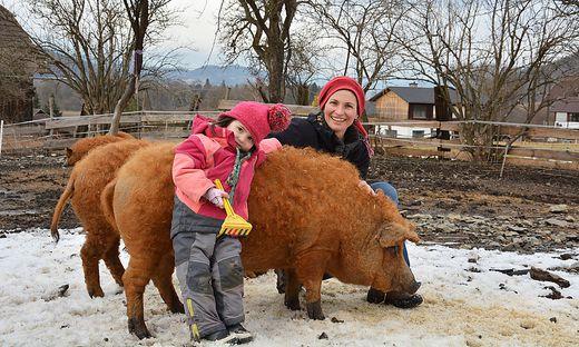 Sonja Herzog mit Tochter Amelie und den Mangalitzer Wollschweinen