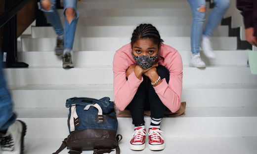 Depressed young student with face mask sitting on floor back at college or university, coronavirus concept.