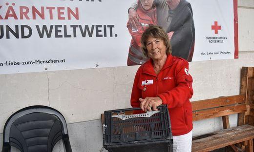 """Helga Rainer bei ihrer Arbeit für die """"Tafel"""", dahinter ein großes Plakat des Roten Kreuzes"""