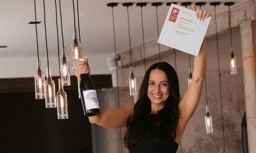 Geschäftsführerin Sarah Puschnegg mit Preis und prämiertem Wein