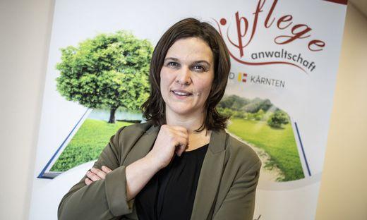 Pflegeanwältin Bettina Irrasch vor einem Plakat in ihren Büroräumlichkeiten