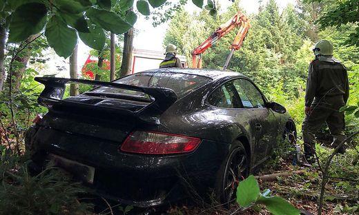 Porsche steht im Wald zwischen Bäumen und Gestrüpp
