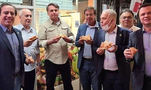 Brasiliens Präsident Jair Bolsonaro mit seiner Entourage beim Pizza-Essen auf dem Gehsteig