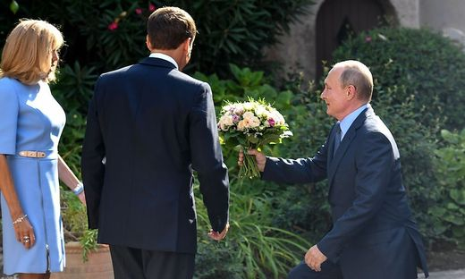 Ganz Gentleman: Putin überreicht Brigitte Macron einen sommerlichen Blumenstrauß beim Arbeitstreffen an der französischen Riviera