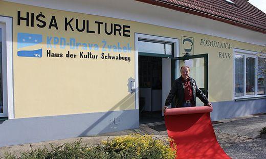 Leonhard Katz, Obmann des Katholischen Kulturvereins Drava, legt für den Bundespräsidenten den roten Teppich aus