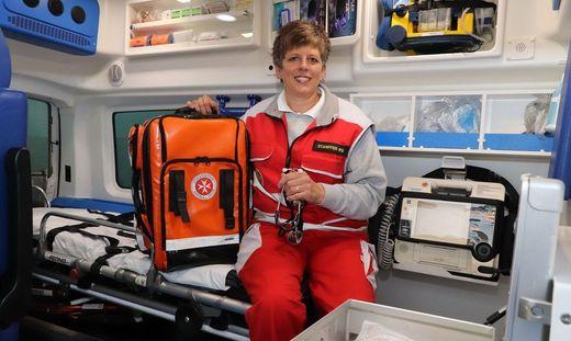 Karin Stampfer sitzt mit der Notfalltasche imRettungswagen der Johanniter