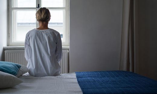 Rear view of woman patient sitting on bed in hospital feeling stressed, mental health and coronavirus concept.