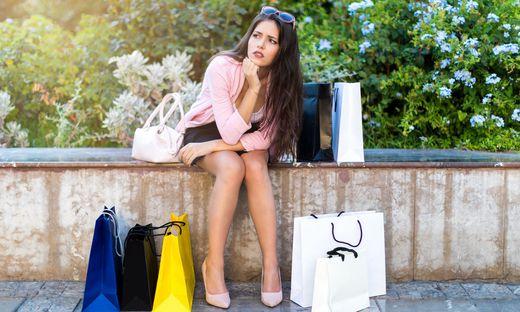 Junge Frau sitzt gut gekleidet mit vielen Einkaufstaschen rundherum auf einer niedrigen Mauer