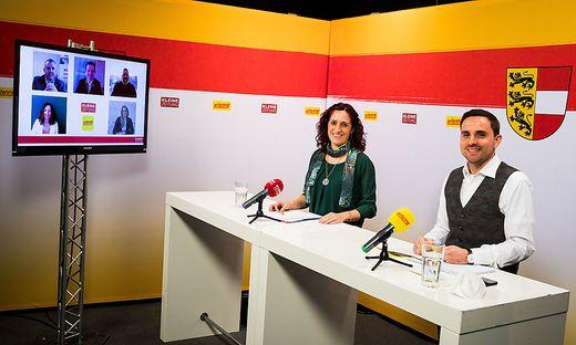 Bettina Friedl (Kleine Zeitung) und Timm Bodner (Antenne Kärnten) mit den Spitzenkandidaten am Bildschirm