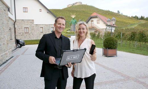 Andy und Kelly Kainz mit Laptop und Handy am Weingut Taggenbrunn
