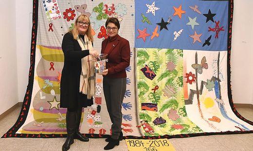 """Michaela Wilhelmer und Beate Prettner vor dem """"Memorial Quilt"""", der an jene 166 Menschen erinnert, die in den letzten 35 Jahren in Kärnten an Aids verstorben sind"""