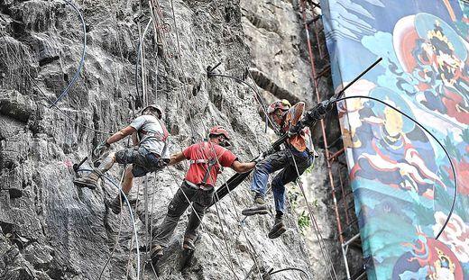 Sämtliche Sanierungsarbeiten werden von den Männern am Seil hängend erledigt, die Arbeiten sind spektakulär anzusehen