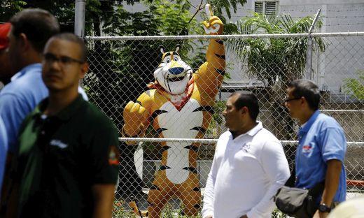 Arbeiter warten in Maracay vor den geschlossenen Toren des Kellogg-Werkes