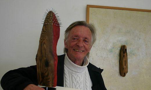 """Gerhard Leeb mit seinem Holzobjekt """"Sinkendes Schlauchboot"""""""
