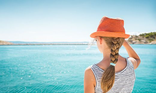 Child girl standing back by the sea - holiday