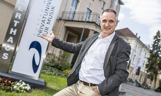 Roland Streiner, frischgebackener Rektor der Musik-Uni, vor dem neuen Logo