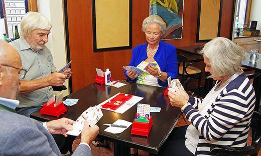 Gespielt wird an mehreren Tischen, wobei zwei Paare gegeneinander spielen