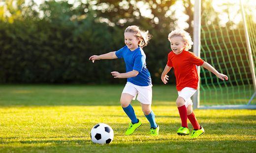 kinder in rot und blau spielen fußball