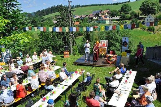 Gäste der Feier sitzen im Garten an Tischen, Gesche Tenzin Dhargye spricht auf einer Bühne, über ihm tibetische Gebetsfahnen