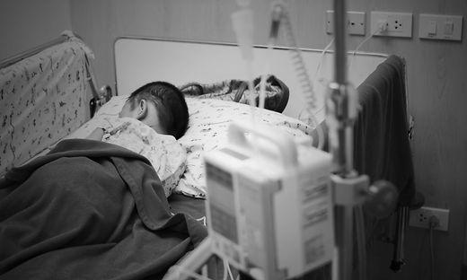 Krankheit brachte viel Schmerz und Kummer in eine Familie, die Eltern pflegen liebevollst ihr Kind (Szene gestellt)