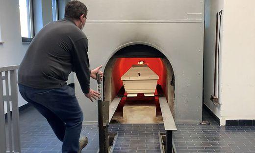 Krematoriums-Mitarbeiter Andreas Bucher fährt einen Sarg in den Ofen ein