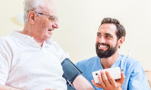 Nurse measuring blood pressure of senior patient