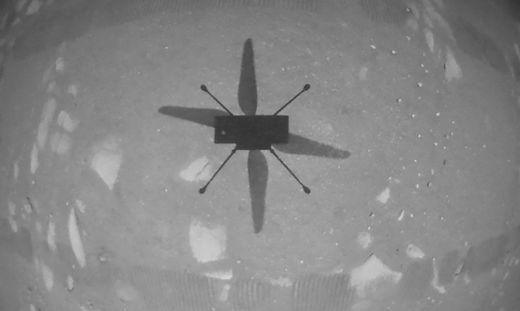 """Auch erste Bilder lagen schon vor: Der Schatten von """"Ingenuity"""" aus der Luft gesehen und der Hubschrauber in der Luft aus der Perspektive des Rovers """"Perseverance"""""""