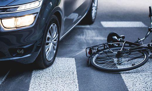 Auto das auf dem Zebrastreifen steht, Rad liegt daneben