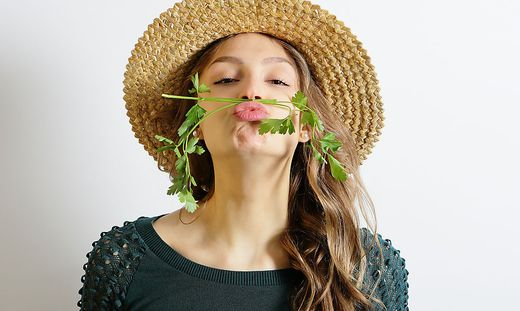 Girl in straw hat with parsley on the face, fun and healthy lifestyle