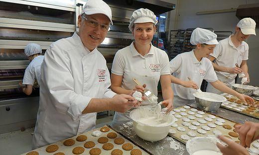 Echte Handarbeit: Michael Regner hilft mit, die Lebkuchen mit Zuckerguss zu überziehen