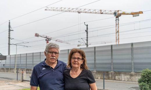 """Heinz und Maria Pichler leben direkt an der Lärmschutzwand, die sie von der Südbahnstrecke abschirmt. Auf der anderen Seite der Bahnstrecke entsteht das Bauprojekt """"Gate 17"""""""