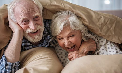 Happy senior husband and wife relaxing in bedroom