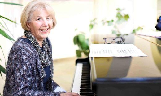 Erika Unterrainer, an einem Klavier sitzend