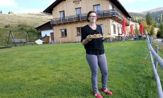 Iris Simma steht mit einem Backhendl am Teller und mit Kartoffelsalat vor der Hütte. Dahinter die Saualpe