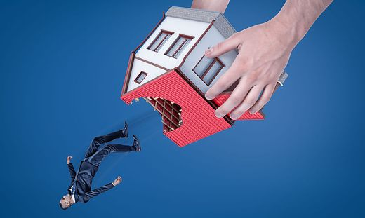 Close-up of man´s hands holding house with hole in roof upside down and dropping out little businessman.